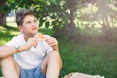 Nett, sitzt Junge im weißen T-Shirt auf dem Gras und nimmt eine Scheibe der Pizza im Sommerpark Junge isst Pizza lizenzfreie stockfotos