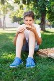 Nett, sitzt Junge im weißen T-Shirt auf dem Gras und nimmt eine Scheibe der Pizza im Sommerpark Junge isst Pizza lizenzfreies stockfoto