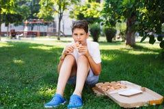 Nett, sitzt Junge im weißen T-Shirt auf dem Gras und nimmt eine Scheibe der Pizza im Sommerpark Junge isst Pizza lizenzfreie stockbilder