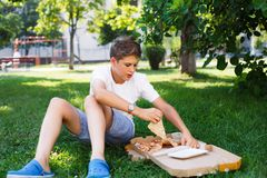Nett, sitzt Junge im weißen T-Shirt auf dem Gras und nimmt eine Scheibe der Pizza im Sommerpark Junge isst Pizza stockfoto