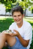 Nett, sitzt Junge im weißen T-Shirt auf dem Gras und nimmt eine Scheibe der Pizza im Sommerpark Junge isst Pizza stockfotografie