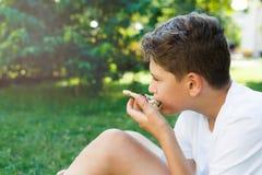 Nett, sitzt Junge im weißen T-Shirt auf dem Gras und nimmt eine Scheibe der Pizza im Sommerpark Junge isst Pizza stockfotos