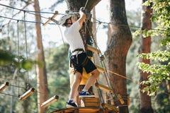 Nett, sportlich, Junge im weißen T-Shirt im Abenteuertätigkeitspark mit Sturzhelm und Schutzausrüstung Junger Junge stockfotografie