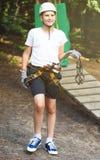 Nett, sportlich, Junge im weißen T-Shirt im Abenteuertätigkeitspark mit Sturzhelm und Schutzausrüstung Junger Junge lizenzfreie stockfotografie