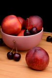 Nettarine e ciliege su una tavola di legno Fotografia Stock