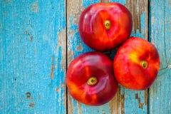 Nettarine piane organiche fresche su un vecchio fondo di legno Fotografia Stock Libera da Diritti