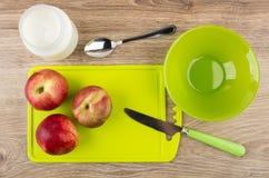 Nettarine sul tagliere, sulla ciotola vuota e sul yogurt in barattolo Fotografie Stock Libere da Diritti