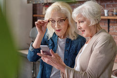 Nette ältere Damen, die modernes Gerät verwenden Stockfoto