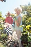 Nette ältere Frau, die ein Laubrechen während der Arbeit im Garten hält Stockfotografie
