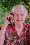 Nette, ältere Frau, die an einem Handy spricht lizenzfreie stockfotografie