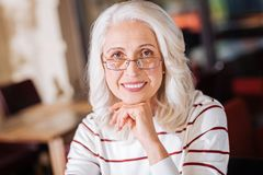 Nette ältere Frau, die friedlich sitzt und lächelt Stockbild