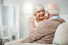 Nette ältere Frau, die ihr Ehemanngesicht betrachtet stockfotos
