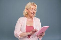 Nette ältere Frau, die Textnachricht von der Tablette sendet lizenzfreie stockbilder