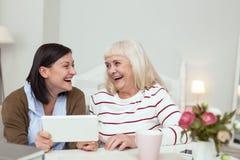 Nette ältere Frau und Pflegekraft, die auf Tablette spielt stockfotos