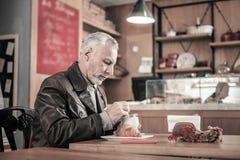 Nette ältere männliche Person, die Lieblingscafé besucht lizenzfreie stockfotografie