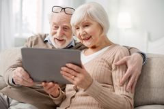 Nette ältere Paare unter Verwendung der modernen Technologie stockfotos