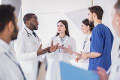 Nette Ärzte, die bei der Konferenz in der Klinik sprechen Stockfotos