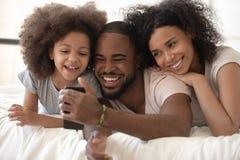 Nette afrikanische Eltern und Kind, die unter Verwendung des Smartphone im Bett lacht stockbild