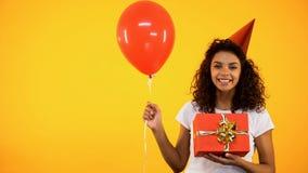 Nette afrikanische weibliche haltene Geschenkbox und Ballon, Geburtstagsfeier feiernd lizenzfreies stockbild
