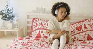 Nette allein stehende Frau in der langen Strickjacke auf Bett Stockbild