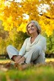 Nette alte Frau, die im Herbstpark sitzt Stockfoto