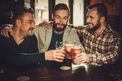 Nette alte Freunde, die Spaß haben und Fassbier in der Kneipe trinken Lizenzfreie Stockbilder