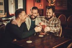 Nette alte Freunde, die Spaß haben und Fassbier in der Kneipe trinken Lizenzfreie Stockfotos