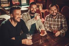 Nette alte Freunde, die Spaß haben und Fassbier in der Kneipe trinken Stockfotos