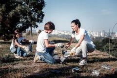 Nette angenehme Kinder, die Abfall sammeln Stockfotos