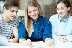 Nette arbeitende und lachende Studenten Lizenzfreie Stockbilder