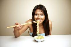 Nette asiatische Frau, die Nudeln isst Stockfotografie