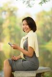 Nette asiatische Frau mit Mobiltelefon Stockfotografie