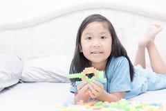 Nette asiatische Mädchenspiel-Blockziegelsteine auf Bett Stockfotos