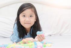 Nette asiatische Mädchenspiel-Blockziegelsteine auf Bett Lizenzfreie Stockfotografie