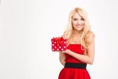 Nette attraktive blonde Frau im roten Kleid, das Geschenk hält Stockfotografie