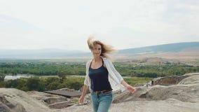 Nette attraktive Dame mit dem langen blonden fliegenden Haar betrachtet herrliche Aussicht von Georgia von der hohen Klippe, wirb stock footage
