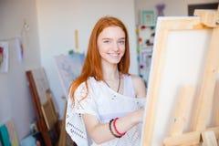 Nette attraktive Künstlerinmalerei auf Segeltuch in der Kunstwerkstatt Lizenzfreie Stockfotos