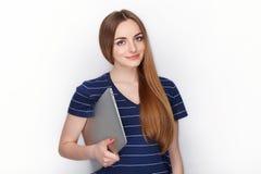 Nette attraktive kaukasische Blondine mit der Anwendung des dünnen eleganten Notebooks lokalisiert auf einem weißen Hintergrund Stockbild