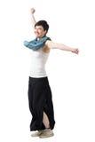 Nette aufgeregte Frau, die mit den angehobenen Armen tragen breite Hosen und Schal spinnt Stockfoto