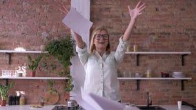 Nette Büroarbeitnehmerin mit den Gläsern, die Papierdokumente werfen und Erfolg des Projektes in der Küche feiern stock video