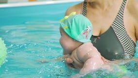 Nette Baby-Schwimmen mit Trainer in einem Pool stock footage