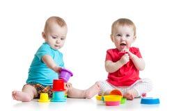 Nette Babys, die mit Farbspielwaren spielen Kindermädchen Lizenzfreie Stockfotos