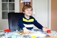 Nette Backenlebkuchen Weihnachtsplätzchen des kleinen Jungen zu Hause Lizenzfreie Stockfotos
