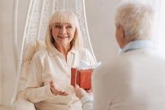 Nette begeisterte Frau, die ein Geschenk empfängt lizenzfreies stockfoto