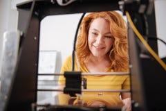Nette begeisterte Frau, einen Drucker 3d in der Arbeit beobachtend Stockbilder