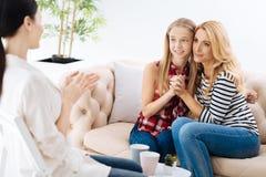 Nette begeisterte Mutter und Tochter, die den Therapeuten betrachtet Lizenzfreies Stockbild