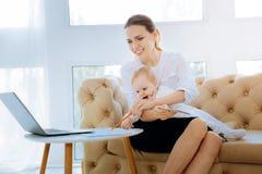 Nette beschäftigte Frau mit einem Kind, das aufgeregt schaut Stockbilder