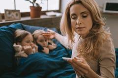 Nette besorgte Mutter, die um ihre kranken Töchter sich kümmert lizenzfreie stockfotos