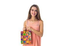 Nette Blicke des jungen Mädchens vorwärts zum Lächeln und zum Halten des bunten hellen Pakets lokalisiert auf weißem Hintergrund Stockbild