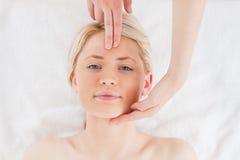 Nette blond-haired Frau, die eine Massage erhält Lizenzfreie Stockfotos